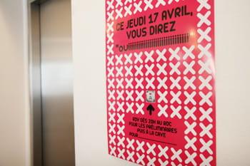 l'affiche d'une soirée corporate à côté des ascenseurs.