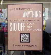 une affiche propose 10$ de remise pour tout achat d'une carte cadeau de 50$