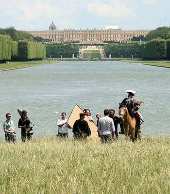 le tournage d'un film d'époque dans le parc du château de versailles.