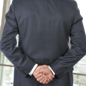 les mains jointes dans le dos sont un signe d'autorité.