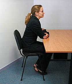 assis, bras croisés, en remuant les pieds :vous êtes sur la défensive.