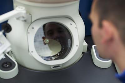 chercheur d'ibm se penchant sur un microscope électronique nanométrique du